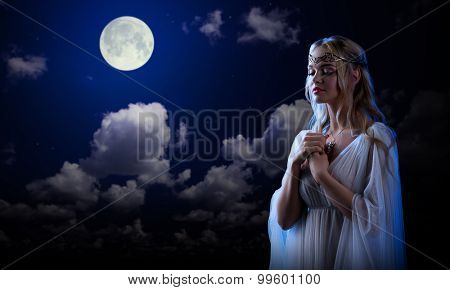 Young elf girl on night sky background