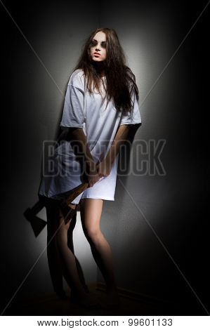 Zombie girl with axe on grey wall