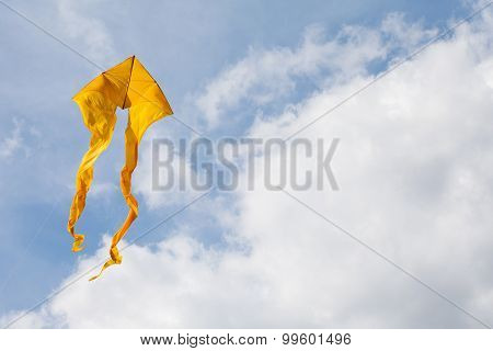 Yellow Kite Flying In The Cloudy Blue Sky. Wind Power