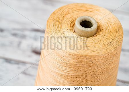 Spool Of Synthetic Orange Thread On White Wooden Background