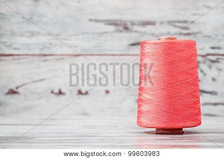 Spool Of Synthetic Pink Thread On White Wooden Background