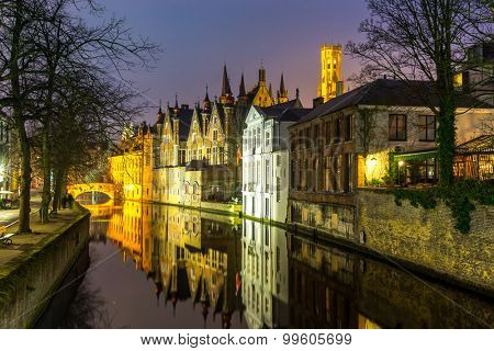 Historic medieval buildings along a canal in Bruges, Belgium at dusk.
