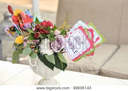 Multicolored fresh flowers bouquet and paper decorations in a vase on a table and tag