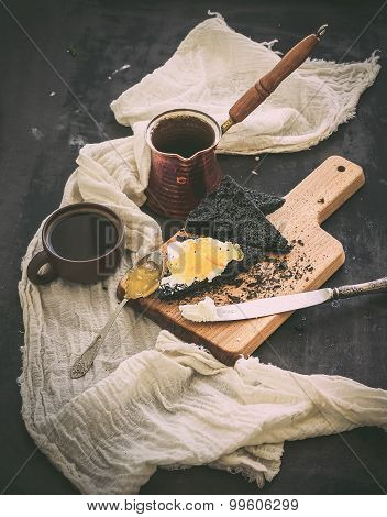 Breakfast set. Coffe, black toasts with cream-cheese and orange marmalade on dark grunge table surfa