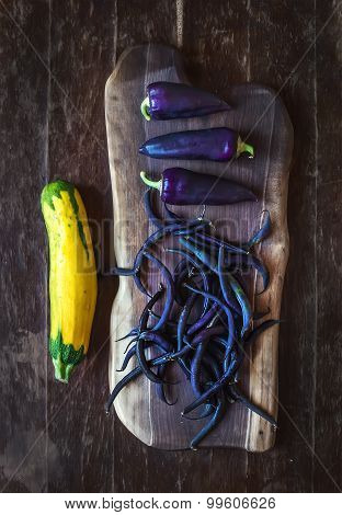 Violet chili peppers, beans and yellow zucchini on rustic wooden chopping board over dark wood backg