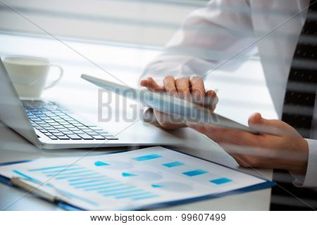 Close-up of hands of business man working on a tablet computer.