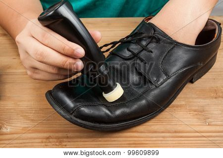 Person Polishing And Restoring Worn Out Shoe With Liquid Shoe Polish