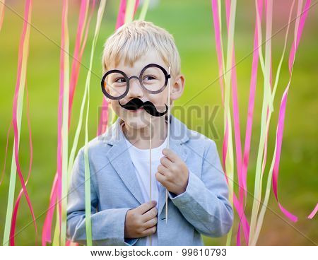 little boy with funny paper mustache and glasses
