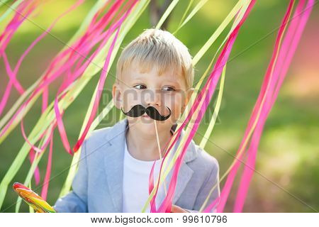 little boy with funny paper mustache
