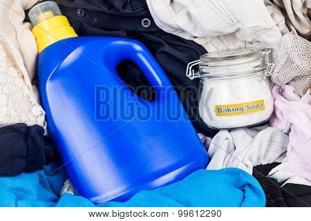 Closeup On Baking Soda With Detergent And Pile Of Dirty Laundry.