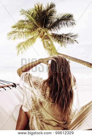 Young beautiful woman relaxing on the hammock under the coconut trees