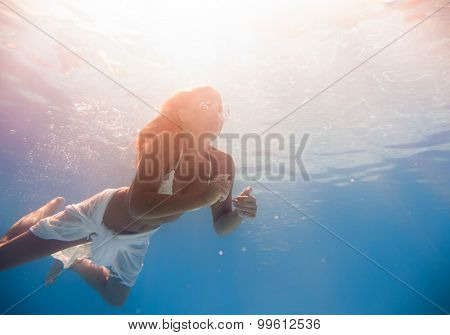 Young woman swimming underwater in the swimming pool