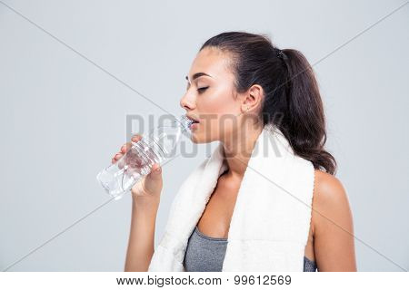 Portrait of a fitness woman with towel drinking water isolated on a white background