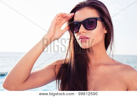 Portrait of a beautiful young girl in sunglasses standing outdoors