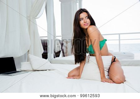 Portrait of a sexy beautiful woman in bikini sitting on the bed and looking away