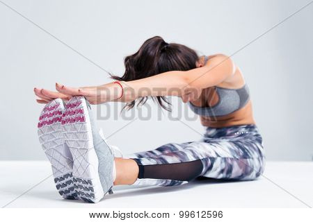 Portrait of a young woman stretching on the floor isolated on a white background