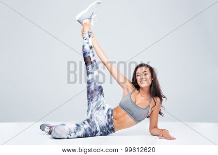 Portrait of smiling fitness woman stretching legs on the floor isolated on a white background