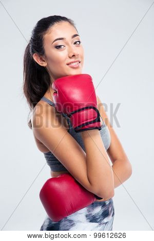 Portrait of a happy beautiful girl with boxing gloves standing isolated on a white background