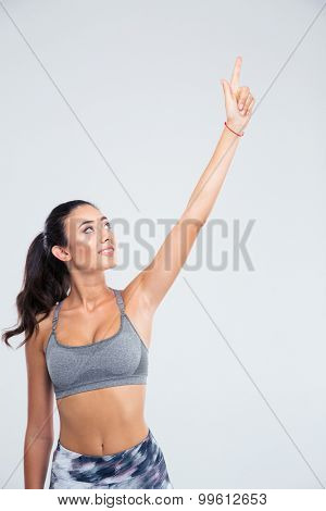 Portrait of a happy fitness woman pointing finger up isolated on a white background