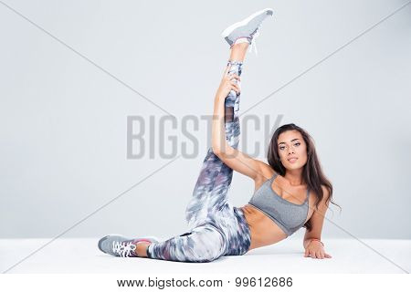 Portrait of lovely fitness woman stretching legs on the floor isolated on a white background