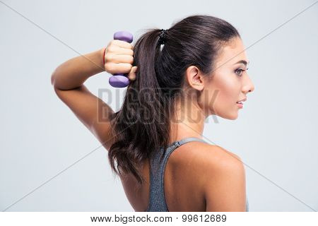 Side view portrait of a beautiful sports woman working out with dumbbells isolated on a white background