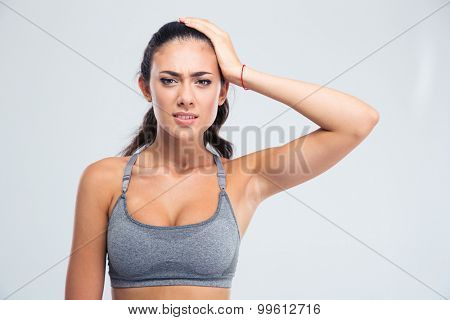 Portrait of a sports woman having headache isolated on a white background. Looking at camera
