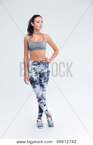 Full length portrait of a sports woman standing isolated on a white background. Looking away