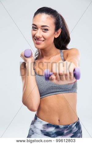 Portrait of a smiling fitness woman workout with dumbbells isolated on a white background. Looking at camera