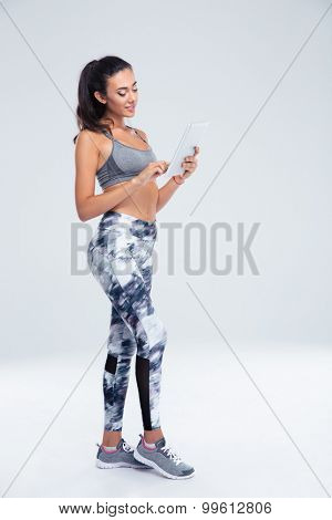 Full length portrait of a beautiful sports woman using tablet computer isolated on a white background