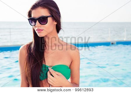 Portrait of a beautiful woman in bikini and sunglasses standing with swim pool on background