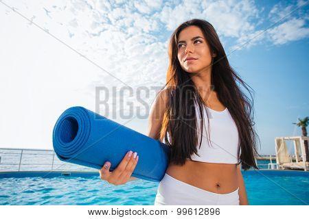 Portrait of a beautiful woman holding yoga mat outdoors