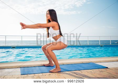 Portrait of a young girl working out on yoga mat outdoors in the morning