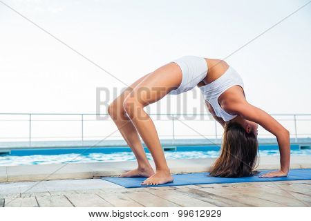 Young girl standing in bridge pose outdoors
