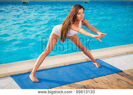 Portrait of a young woman doing yoga exercises on mat outdoors in the morning