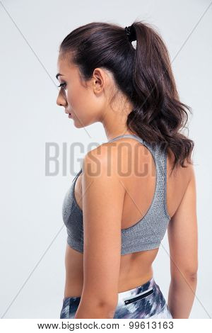 Side view portrait of a fitness woman standing isolated on a white background