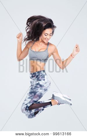 Full length portrait of attractive sports woman jumping isolated on a white background