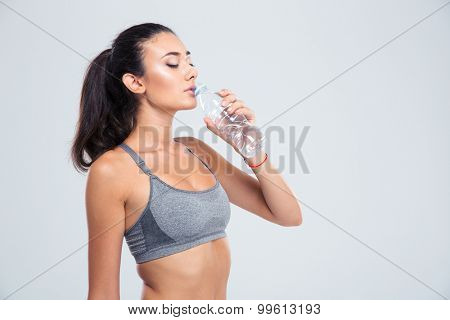 Portrait of a beautiful sports woman drinking water isolated on a white background