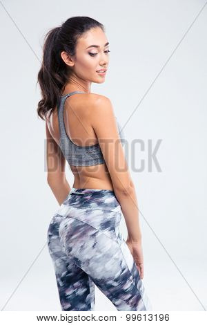 Back view portrait of a happy sports woman posing isolated on a white background