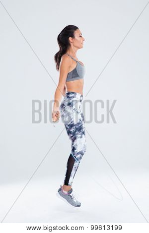 Full length portrait of a fitness woman jumping on skipping rope isolated on a white background