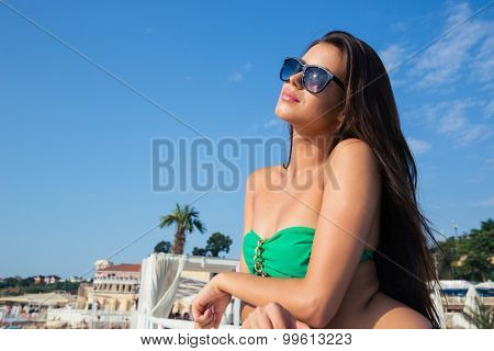Portrait of a beautiful woman in bikini standing outdoors and looking away