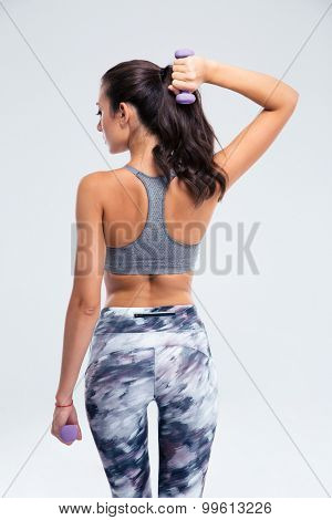 Back view portrait of a fitness woman working out with small dumbbells isolated on a white background