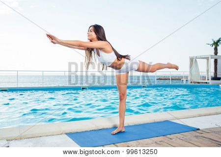 Portrait of a young girl doing stretching exercises outdoors in the morning