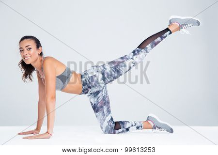 Portrait of happy fitness woman stretching legs on the floor isolated on a white background