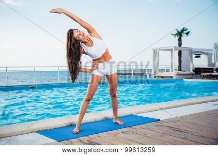 Portrait of a young girl doing yoga exercises outdoors in the morning