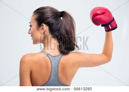 Back view portrait of a sports woman standing with boxing gloves in victory pose isolated on a white background
