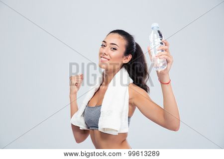 Portrait of a cheerful sports woman with towel holding bottle with water isolated on a white background