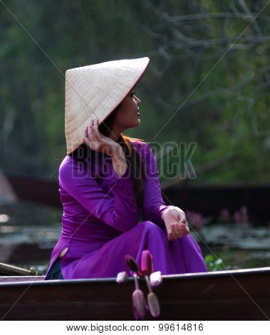 Vietnamese girl wear Ao dai and sits on boat in Yen stream to Huong pagoda in Ha