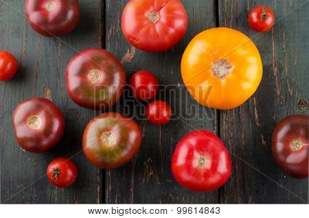 Colorful different kinds of tomatoes on wooden background