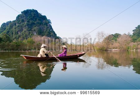 ietnamese girl wear Ao dai and sits on boat in Yen stream to Huong pagoda in Han