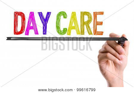 Hand with marker writing the word Day Care